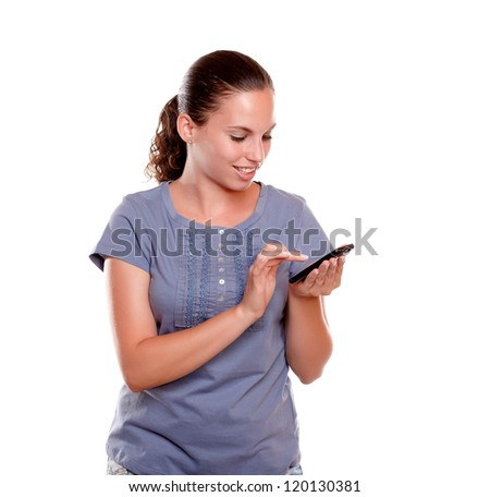 Charming young female sending message by cellphone on blue shirt standing over white background - stock photo