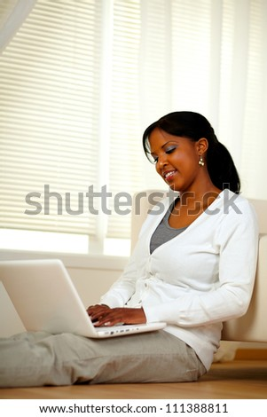 Charming young female working on laptop while sitting on the floor at home indoor. With copyspace - stock photo