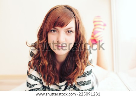 Charming young ginger woman lying on a carpet in the living room. Photo toned style Instagram filters. - stock photo
