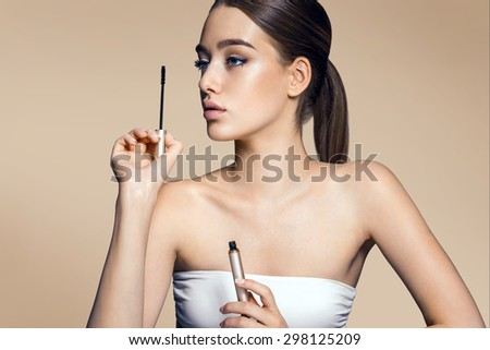 Charming young girl applying mascara / photos of appealing brunette girl on beige background - stock photo