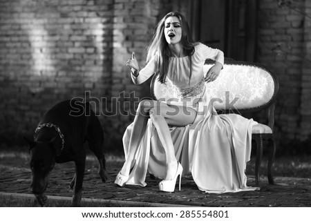Charming young girl in beautiful evening dress sitting on sofa outdoor with dog breed mastiff on natural background black and white, horizontal picture - stock photo
