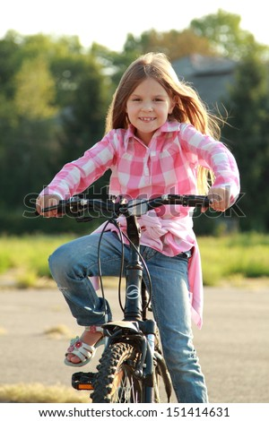 Charming young girl in blue jeans rides a bicycle in a park on a sunny day/Caucasian smiling child playing sports on a bicycle in a park outdoors - stock photo