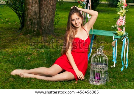 Charming young girl in red dress lying on the grass during summer. Full - length