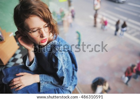Charming young girl with glasses and blue jeans dress sitting by the large window in the room behind the glass on urban street people.