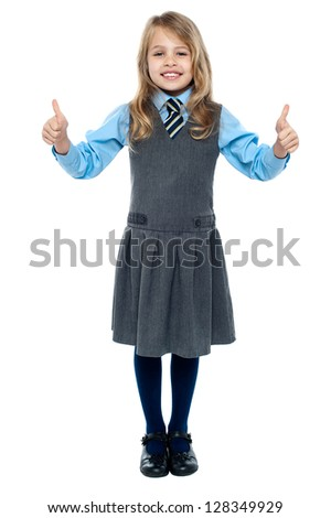 Charming young kid in school uniform showing double thumbs up sign. - stock photo