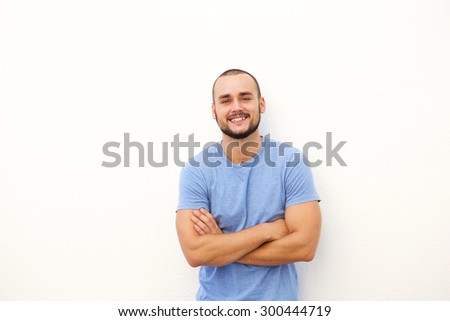 Charming young man smiling against white background with arms crossed - stock photo