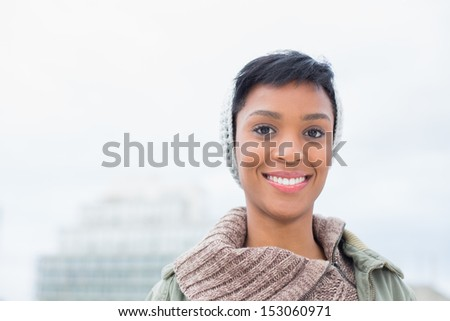 Charming young model in winter clothes posing outside on a cloudy day - stock photo