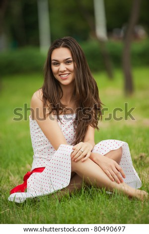 Charming young smiling woman in white clothes, in park