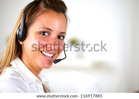 Charming young smiling woman using headphones and looking at you