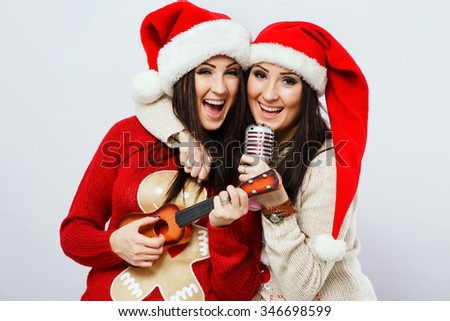 Charming young twins, wearing in colorful sweaters, jeans and red santa hats, holding microphone and ukulele in their hands and singing, on white background, in studio, waist up - stock photo