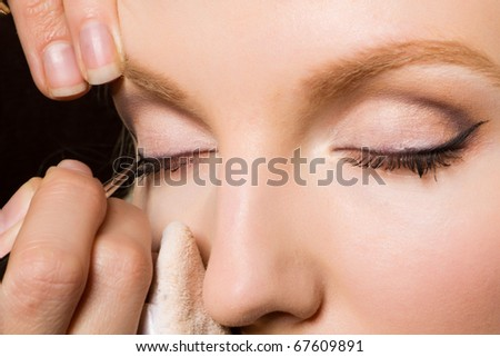 Charming young woman applying blusher eyelid - stock photo
