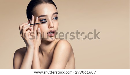 Charming young woman applying mascara / photos of appealing brunette girl on beige background - stock photo