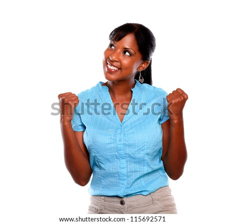 Charming young woman celebrating a victory on blue shirt against white background - copyspace - stock photo