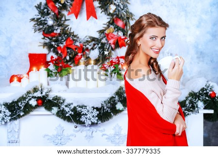 Charming young woman celebrating Christmas at home by a fireplace, beautifully decorated for Christmas. - stock photo