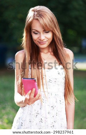 Charming young woman close-up in white dress reads message to mobile phone, against green of summer park. - stock photo