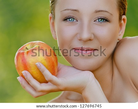 Charming young woman close up with bare shoulders holding an apple, against background of summer green park. - stock photo