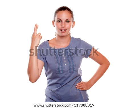 Charming young woman crossing her fingers on blue shirt on isolated background - stock photo