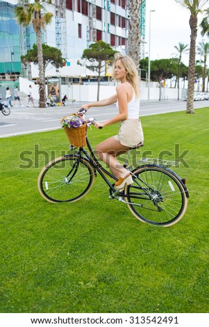 Charming young woman cyclist enjoy the riding in the park on her vintage bike with a basket of flowers, female ride on bicycle over a green lawn background with copy space area for your text message - stock photo