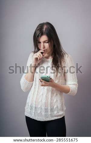 Charming young woman dial SMS to mobile phone - stock photo
