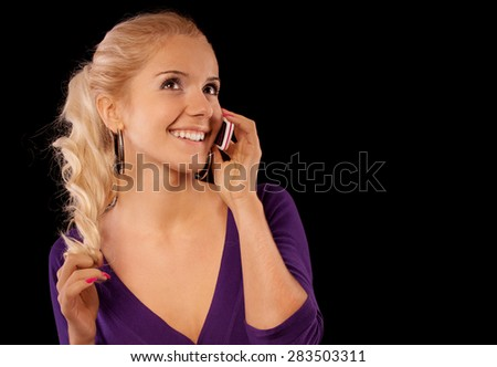 Charming young woman discusses by mobile phone family problems, isolated on black background. - stock photo