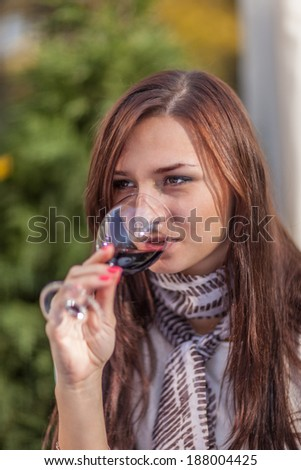 Charming young woman drinking red wine - stock photo