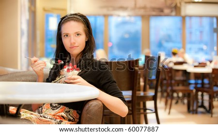 Charming young woman eats dessert in cafe. - stock photo