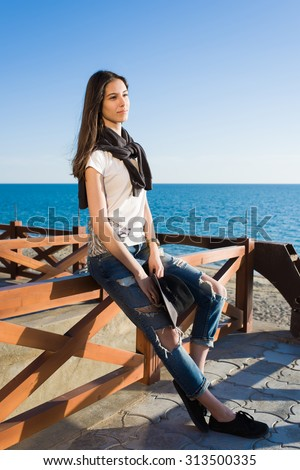 Charming young woman enjoying a good weather and recreation time while sitting against the sea in sunny afternoon, stylish female hipster rest after strolling along the beach in spring season - stock photo