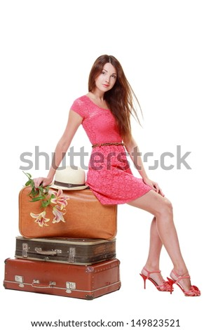 charming young woman in a summer dress sitting on old suitcase isolated on white on a travel theme