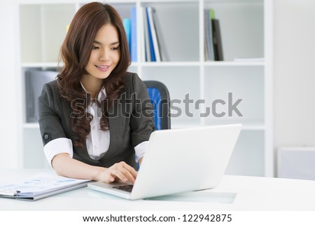 Charming young woman in formalwear computing in office - stock photo