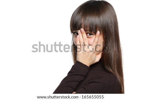 Charming young woman peeking though her fingers over white background - stock photo