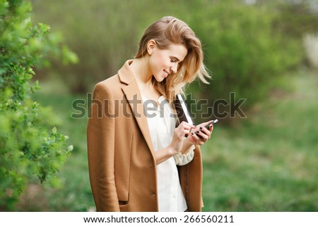 Charming young woman reads message to mobile phone, against green of summer park. - stock photo