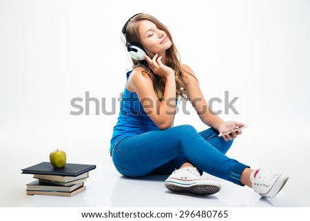 Charming young woman sitting on the floor and listening music on smartphone isolated on a white background - stock photo