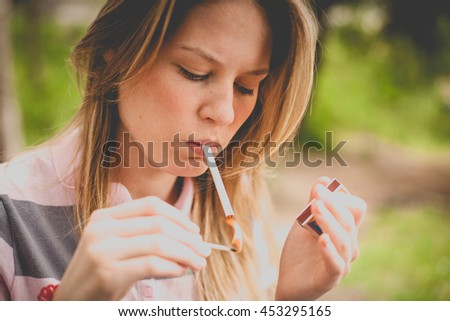 charming young woman smoking a cigarette nature outdoors, family problems, domestic violence, a way to keep the mind. vintage yellow colors - stock photo
