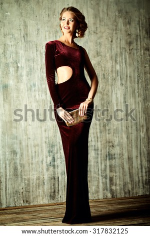 Charming young woman wearing elegant evening dress and beautiful hairstyle. Jewellery.  Fashion shot. Full length portrait. - stock photo