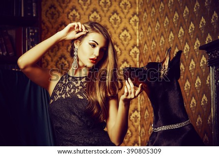 Charming young woman with her dog in a room with luxurious classic interior. Fashion. - stock photo