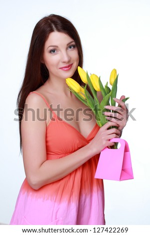 Charming young woman with natural bouquet of flowers/Studio portrait of lovely girl with natural yellow tulips on Beauty and Fashion theme