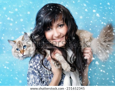 Charming young woman with siberian cat in snow - stock photo