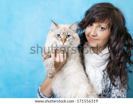 Charming young woman with Siberian cat on blue background - stock photo