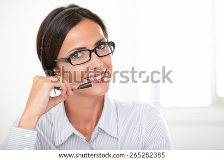 Charming young woman with spectacles speaking on headphones while cheerfully looking at you - copyspace - stock photo