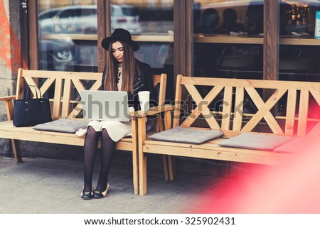Charming young woman with trendy look work on portable laptop computer during coffee break outdoors,gorgeous female freelancer using net-book for remote job while sitting on the bench in sidewalk cafe - stock photo