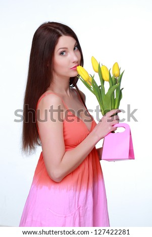 Charming young woman with yellow tulips and gift on Holiday/Pretty girl holding small pink bag