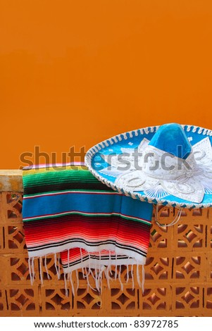 charro mariachi blue mexican hat and serape poncho over orange tiles wall - stock photo
