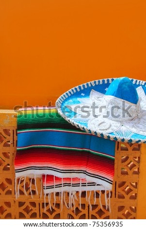 charro mariachi blue mexican hat serape poncho over orange tiles wall - stock photo