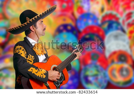 Charro Mariachi playing guitar over colorful blur handcrafts background  [Photo Illustration] - stock photo
