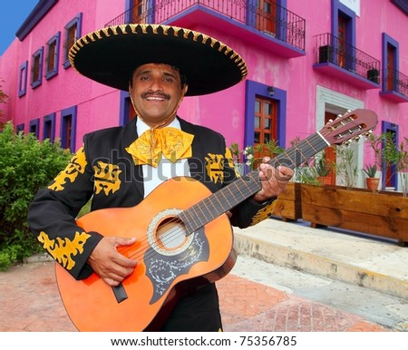 Charro Mariachi singer playing guitar in Mexico houses background - stock photo