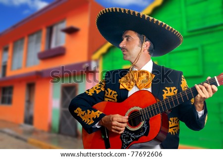 Charro Mariachi singer playing guitar in Mexico houses background [Photo Illustration] - stock photo