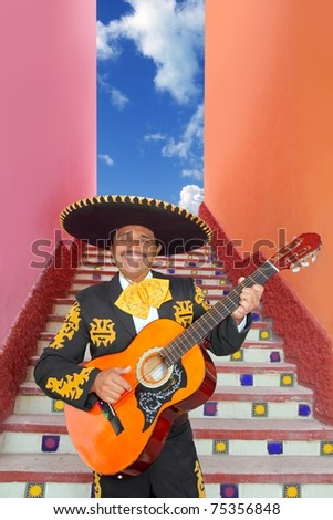 Charro Mariachi singer playing guitar in Mexico stairway - stock photo