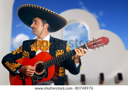 Charro Mariachi singer playing guitar in Mexico with white house background [Photo Illustration] - stock photo