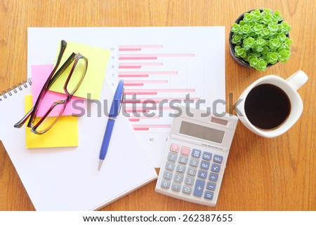 chart and calculator on the wooden table with hot coffee