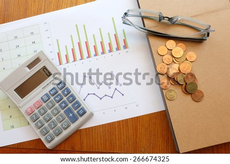 chart and calculator on wooden table with coin  - stock photo